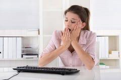 年轻女商人坐疲倦的和打呵欠在办公室 库存照片
