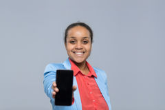 年轻女商人展示细胞聪明的电话空的屏幕非裔美国人的女孩愉快的微笑女实业家 图库摄影