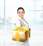 女商人愉快的微笑举行金黄礼物盒 免版税图库摄影