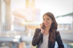 女商人愉快的微笑画象谈话在智能手机机智 图库摄影
