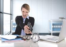 女商人愤怒和恼怒与指向枪的计算机膝上型计算机一起使用闹钟 免版税图库摄影