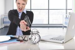 女商人愤怒和恼怒与指向枪的计算机膝上型计算机一起使用闹钟 库存照片