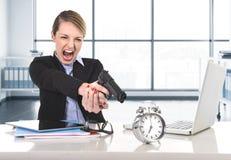 女商人愤怒和恼怒与指向枪的计算机膝上型计算机一起使用闹钟 免版税库存图片