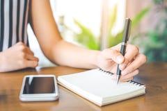 女商人手在与笔的一个笔记薄书写在办公室 免版税库存图片