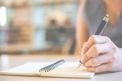 女商人手在有笔的一个笔记本书写 免版税图库摄影