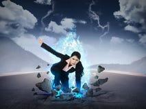 女商人拳打有蓝色火力的路 免版税库存图片