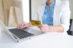 女商人拿着信用卡和使用膝上型计算机的办公室领导的图象为网络购物 图库摄影