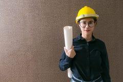 女商人拿着在backgroun的工程师开发商图纸 免版税库存照片