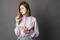 女商人拿着有笔的一个笔记本 某事写并且认为 背景画笔关闭查出摄影白色的工作室牙 一在灰色背景 免版税图库摄影