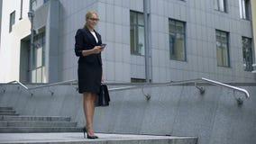 女商人接受在手机的通知关于聘用,促进 股票录像