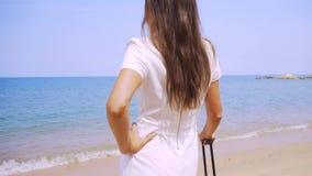女商人沿美丽的海的岸带着手提箱的走 女性腿走带着手提箱的岸 影视素材