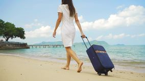 女商人沿美丽的海的岸带着手提箱的走 自由职业者的概念,期待已久的休闲概念 股票视频