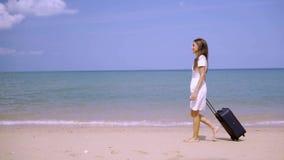女商人沿美丽的海的岸带着手提箱的走 自由职业者的概念,期待已久的休闲概念 股票录像