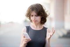 年轻女商人激怒与她的电话 库存图片