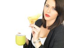 年轻女商人用咖啡和热的涂奶油的多士 免版税库存图片