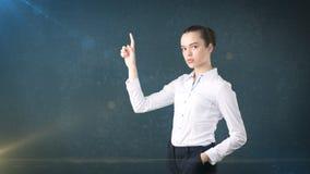 女商人用在按一个无形的按钮,被隔绝的演播室背景的白色裙子的小圆面包 到达天空的企业概念金黄回归键所有权 免版税图库摄影