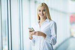 女商人用途或键入在大办公室窗口附近的电话在现代聪明的空间 免版税库存图片