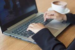 女商人用途的手对工作的一台膝上型计算机在办公室用热的咖啡 图库摄影