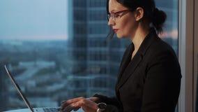 女商人画象戴眼镜的在办公室 坐在桌上和研究膝上型计算机的女孩 股票录像