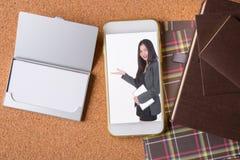 女商人的图片巧妙的电话和空白的名片的和 图库摄影