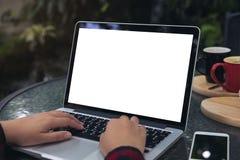 女商人的大模型图象使用和键入在有空白的白色屏幕、巧妙的电话和咖啡杯的膝上型计算机的在玻璃桌上 库存照片