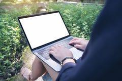 女商人的大模型图象使用和键入在有空白的白色桌面屏幕的膝上型计算机的,坐在室外与自然 免版税图库摄影