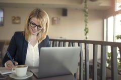 女商人研究计算机,采取笔记,考虑某事在咖啡店,餐馆 免版税库存照片