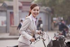年轻女商人站立与自行车的,北京,中国 库存照片