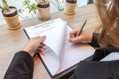 女商人签署的合同文件形式 免版税库存图片