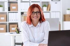 女商人红头发人办公室画象坐桌 图库摄影