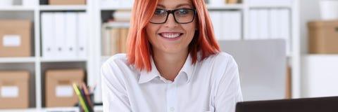 女商人红头发人办公室画象坐桌 免版税库存照片