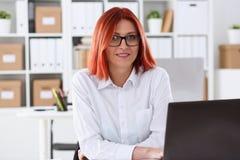 女商人红头发人办公室画象坐桌 库存图片