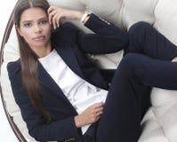 女商人认为,坐在一把圆的椅子 免版税库存图片