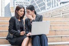 女商人说闲话,当使用膝上型计算机在室外时 事务和工友概念 库存图片