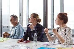 女商人谈论项目在会议期间在现代办公室 库存图片