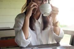 女商人谈话在手机,当拿着咖啡杯时 库存照片
