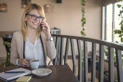 女商人谈话在智能手机和采取笔记,在咖啡店,餐馆 库存照片