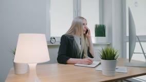 女商人谈话在智能手机在办公室 坐在工作场所的办公室衣服的典雅的年轻白肤金发的女性和 股票录像
