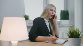 女商人谈话在智能手机在办公室 坐在工作场所的办公室衣服的典雅的年轻白肤金发的女性和 股票视频