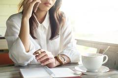 女商人谈话在电话,当候宰栏为做a没有时 库存图片