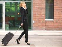 女商人走与行李和谈话在电话 免版税库存图片