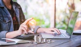 女商人递拿着在堆硬币的电灯泡和与在工作场所的计算机一起使用 挽救星期一的创造性的想法概念 免版税库存照片