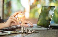 女商人递拿着在堆硬币的电灯泡和与在工作场所的计算机一起使用 挽救星期一的创造性的想法概念 库存照片