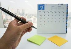 女商人遇见的提示举行笔在2月日历 库存图片