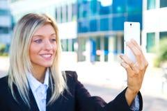 女商人采取与她的手机的一selfie 免版税库存图片