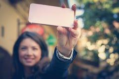 女商人采取与巧妙的电话的一张自画象 图库摄影