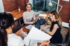 女商人队与纸一起使用使用坐在书桌的膝上型计算机在办公室 库存图片