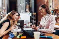 女商人队与纸一起使用使用坐在书桌的膝上型计算机在办公室 免版税库存照片