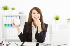 年轻女商人饮用的咖啡在办公室 库存照片
