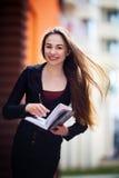 年轻女商人,保留一笔记本,笔和微笑 免版税库存图片